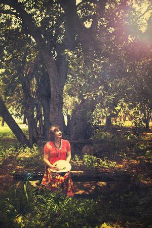 femme d'âge mûr assis par le vieil arbre de hauteur sur le banc antique dans le jardin d'été avec un effet vintage.