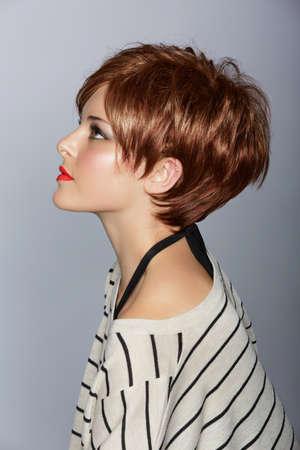 a bob: perfil de una hermosa mujer con labios rojos y pelo corto con plumas de color rojo en el moderno estudio de Bob sobre el fondo Foto de archivo