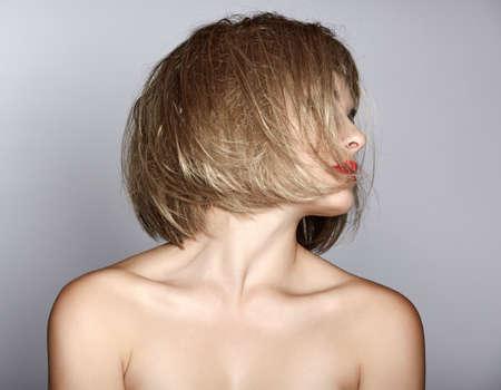 portrait d'une belle femme blonde à court bob avec désordre cheveux mouillés sur fond de studio