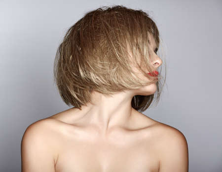 portrait of a beautiful woman in short blond bob with messy wet hair on studio background