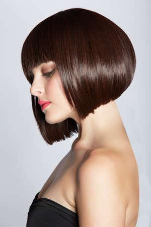 Porträt einer schönen Frau in kurzen Bob Brünette mit ordentlich sauber Haare auf Studio-Hintergrund