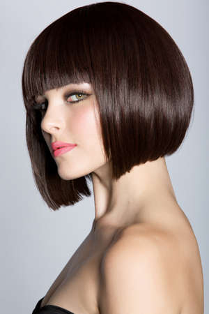 wig: portrait of a beautiful woman in short brunette bob with neat clean hair on studio background