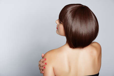 portrait of a beautiful woman in short brunette bob with neat clean hair on studio background photo