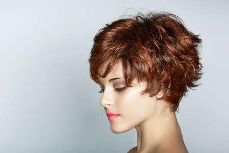 短い茶色の髪と美しい若い女性がコピー スペースでスタジオ背景にピンクの口紅を着ています。