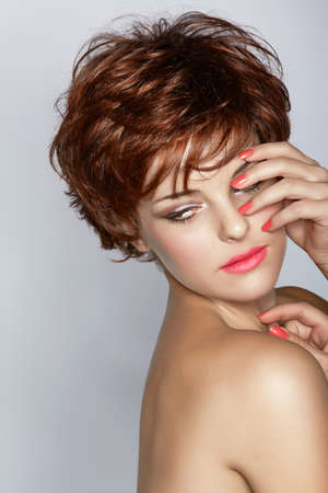 beautiful young woman with short brown haircut wears pink lipstick on studio background with copy space  photo