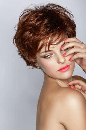 belle jeune femme avec coupe de cheveux courts bruns porte rouge à lèvres rose sur fond de studio, avec copie espace Banque d'images