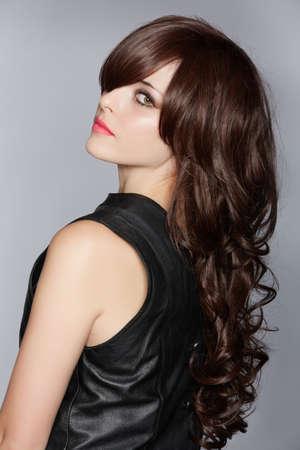 femme avec de longs cheveux bruns bouclés avec un éclat sain, vêtue d'une robe en cuir sur un fond studio de Banque d'images