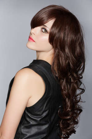 wig: woman with long brown curly hair with healthy shine, wearing a leather dress over a studio background
