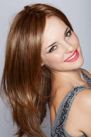 portrait d'une belle femme avec de longs cheveux bruns regardant par-dessus son épaule avec un sourire sur un fond de studio