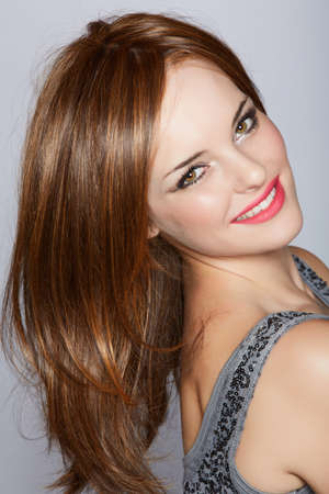 wig: portrait of a beautiful woman with long brown hair looking over her shoulder with a smile over a studio background