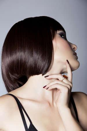 portrait d'une femme belle à court bob brune avec les cheveux propres soignée sur fond de studio - se concentrer sur l'oeil et la peau du visage
