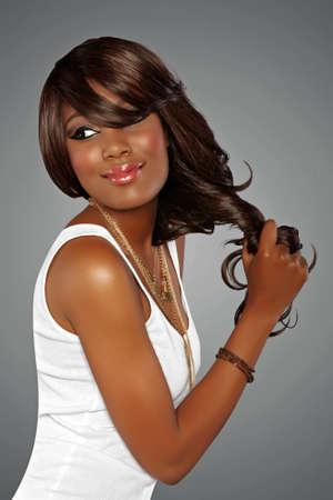 glitter makeup: joven y bella mujer africana con el pelo largo en fondo del estudio Foto de archivo