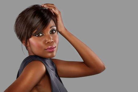 belle jeune femme africaine avec des cheveux longs sur fond de studio