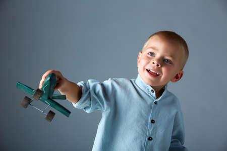 jeune garçon de 3 ans portant une chemise bleu jouant avec un avion jouet en bois à la main, sur fond de studio bleu avec espace pour le texte