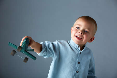 3 year old boy: young 3 year old boy wearing blue shirt playing with wooden toy airplane in his hand on blue studio background with space for text