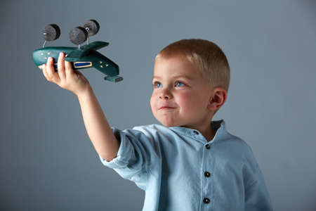 yuong 3 year old boy wearing blue shirt playing with wooden toy airplane in his hand on blue studio background