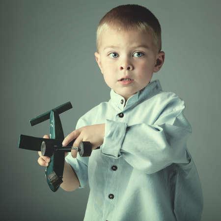 jeune garçon de 3 ans portant une chemise bleu jouant avec un avion jouet en bois à la main, sur fond de studio bleu