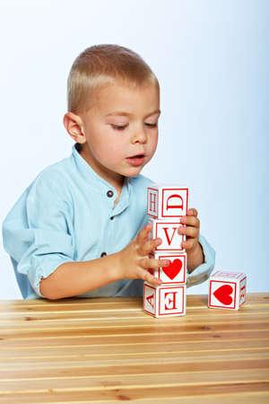 early learning: poco ni�o de 3 a�os ni�o jugando con bloques de madera alfabeto en el estudio de antecedentes de color azul claro Foto de archivo