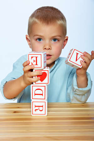little 3 year old toddler boy playing with wooden abc alphabet blocks on the light blue studio background  photo