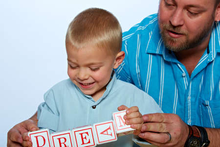 little 3 year old toddler boy and his father playing with wooden abc alphabet blocks on studio background  photo