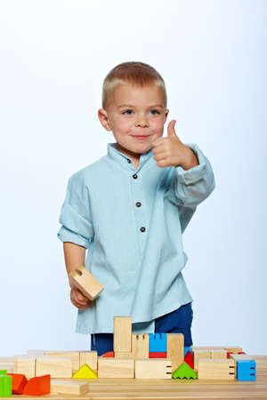 little 3 year old toddler boy playing with bright wooden blocks on a wooden table over light blue studio background photo
