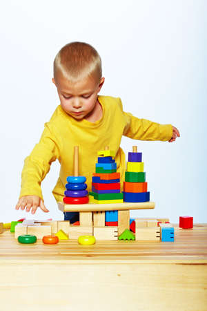 little 3 year old toddler boy playing with bright wooden pyramid over light studio background  photo