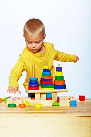 peu 3 garçon bambin ans jouant avec pyramide en bois clair sur fond de studio de lumière Banque d'images