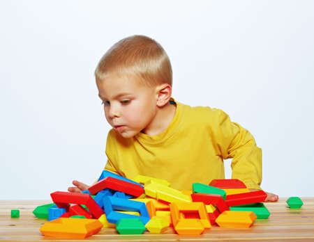 3 year old: little 3 year old toddler boy playing with bright plastic pyramid blocks over light studio background  Stock Photo
