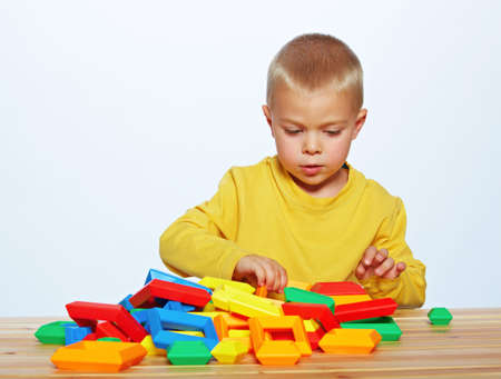 little 3 year old toddler boy playing with bright plastic pyramid blocks over light studio background Stock Photo - 14683813