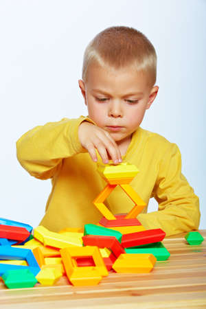 little 3 year old toddler boy playing with bright plastic pyramid blocks over light studio background  Stock Photo - 14683823