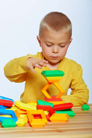 children playing with toys: little 3 year old toddler boy playing with bright plastic pyramid blocks over light studio background  Stock Photo
