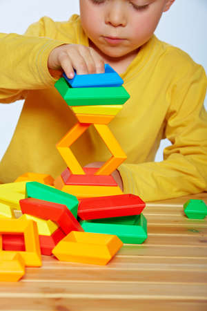 little 3 year old toddler boy playing with bright plastic pyramid blocks over light studio background Stock Photo - 14683821