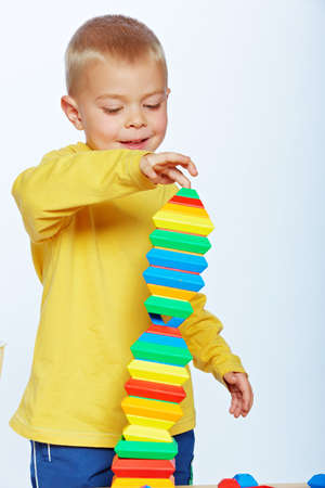 little 3 year old toddler boy playing with bright plastic pyramid blocks over light studio background  photo