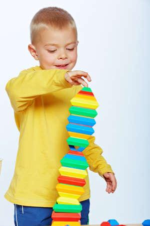 peu 3 garçon bambin ans jouant avec des blocs lumineux pyramide en plastique sur fond de studio de lumière