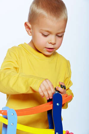 little 3 year old toddler boy playing with wooden cars on studio background Stock Photo