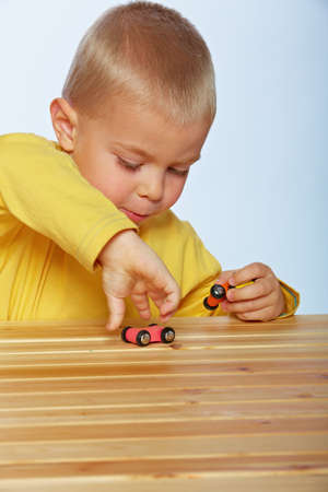 little 3 year old toddler boy playing with wooden cars on studio background Stock Photo - 14683827