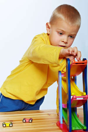 little 3 year old toddler boy playing with wooden cars on studio background photo