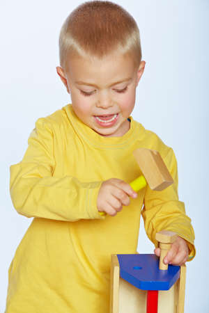 little 3 year old toddler boy with a toy wooden hammer photo