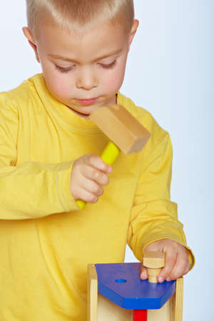educational tools: little 3 year old toddler boy with a toy wooden hammer and toolbox over studio background Stock Photo