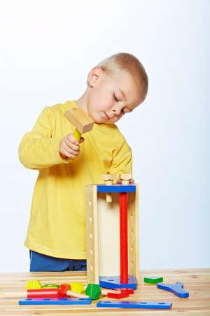 peu 3 toddler boy ans avec un marteau jouet en bois et boîte à outils sur fond de studio Banque d'images