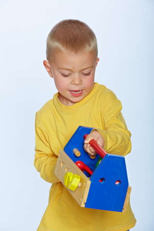 little 3 year old toddler boy with a wooden toolbox and tools over studio background photo