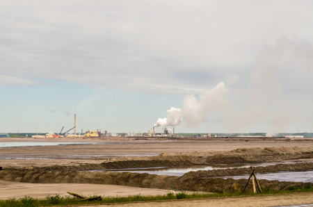 The largest Canadian oil refinery in the background, oil sand in the foreground, smoking pipes