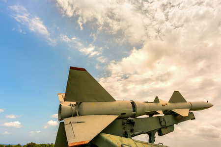 Military weapons, ballistic, anti-aircraft, medium-range missile complexes of ground-based in green grass, directed to the blue sky with white clouds. Фото со стока