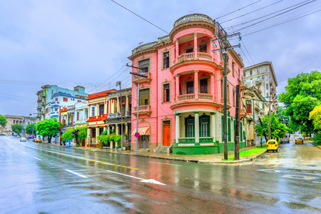 Ancient multi-colored buildings with columns on the street of Cuban Havana at noon after rain, asphalt and blue sky Standard-Bild