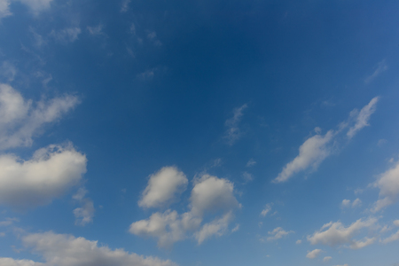 A huge, endless blue sky and white clouds, illuminated by the noon sun