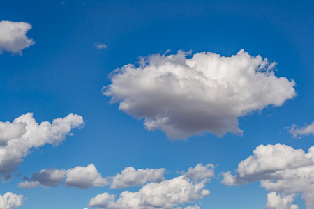 Atmospheric phenomenon, lush, white cumulus clouds against the blue sky on a clear summer day