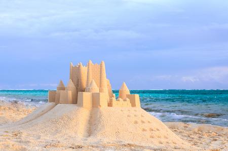 A sand castle on a tropical beach near the ocean at dawn