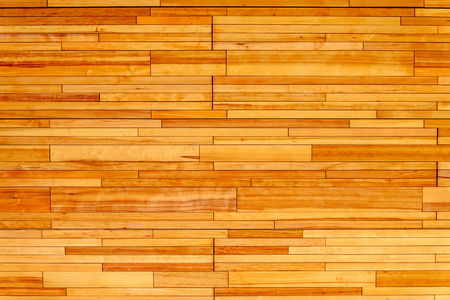 Wooden wall made of rectangular pieces of light wood, varnished