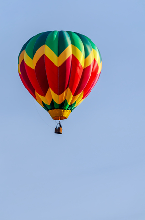 a colorful balloon with a basket, a flame of fire and a silhouette of a pilot flies in a blue sky