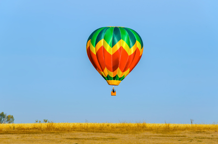 a multi-colored balloon with a basket, a flame of fire and a silhouette of a pilot takes off into the blue sky over the yellow field on a summer day Stock Photo